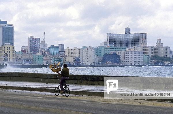 Mann transportiert kleines Schiffsmodell auf Fahhrad  Uferstraße Malecon  Blick auf modernes Stadtviertel Vedado  Havanna  Kuba  Karibik