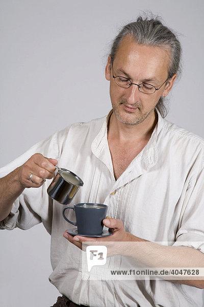 Mann gießt Milch in Kaffeetasse