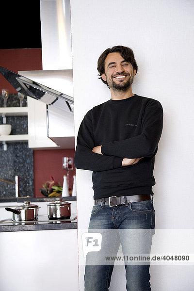 Mann steht in seiner neuen Küche