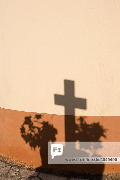 Schatten eines Grabkreuzes an einer Wand