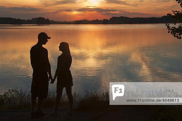 Junges Liebespaar im Sonnenuntergang am Seehamer See  Oberbayern  Bayern  Deutschland  Europa