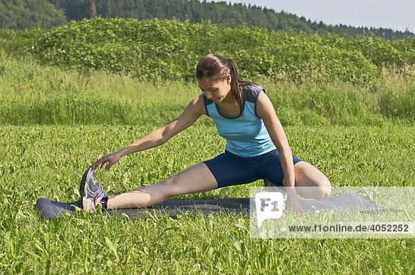 Junge Frau bei gymnastischen Übungen  Stretching