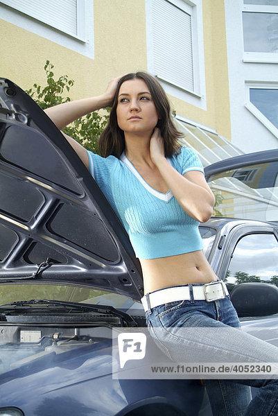 Junge Frau wartet bei ihrem defekten und qualmenden Auto auf Hilfe