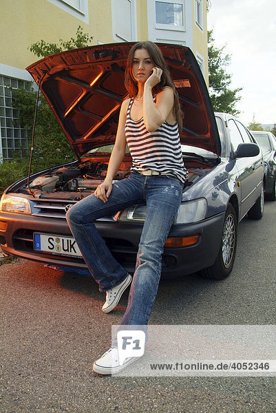 Young woman sitting on her broken down car phoning someone for help