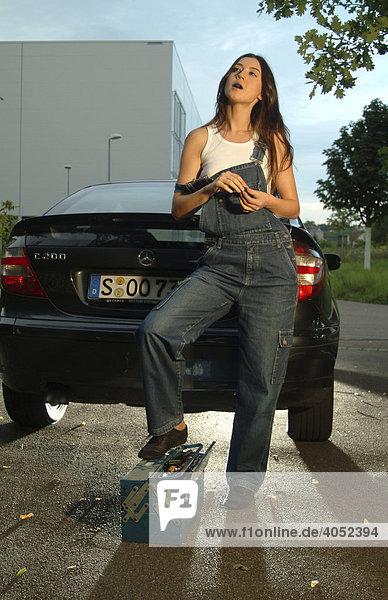 Junge Frau in Arbeitskleidung und mit Werkzeugkasten bei der Reparatur ihres Autos