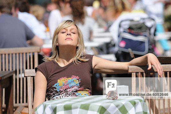 Junge blonde Frau sitzt in einem Café im Sonnenschein  sonnt sich  entspannt