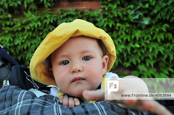 Baby  8 months old  wearing a yellow sun hat  reaching for something towards the camera