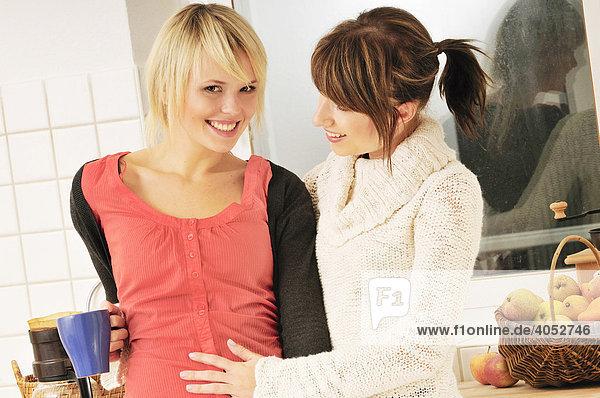 Junge blonde schwangere Frau mit einer Freundin bei einer Kaffeepause