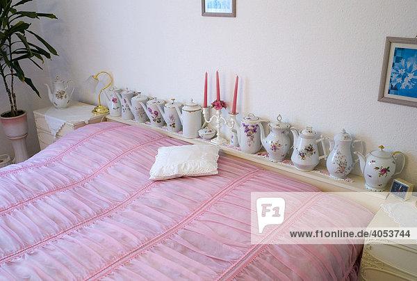 Altmodisches Schlafzimmer mit rosa Bettdecke und Teekannen  Deutschland  Europa