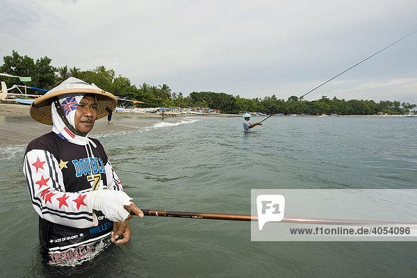 Fischer steht mit Angel im Meer  Insel Lombok  Region kleine Sunda-Inseln östlich von Bali  Republik Indonesien  Asien