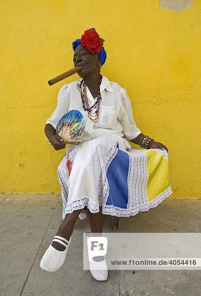Woman with a cigar posing for tourist photographs  historic city centre of Havana  Cuba  Caribbean