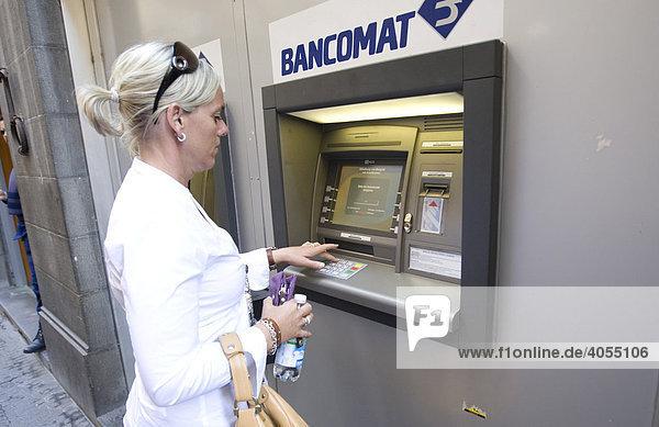 Frau zieht Bargeld an einem Geldautomaten in Siena  Siena  Toskana  Italien  Europa