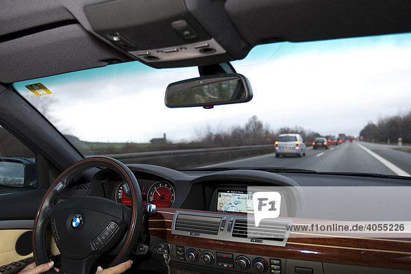 Frau fährt mit Navigationsgerät auf der rechten Spur der Autobahn