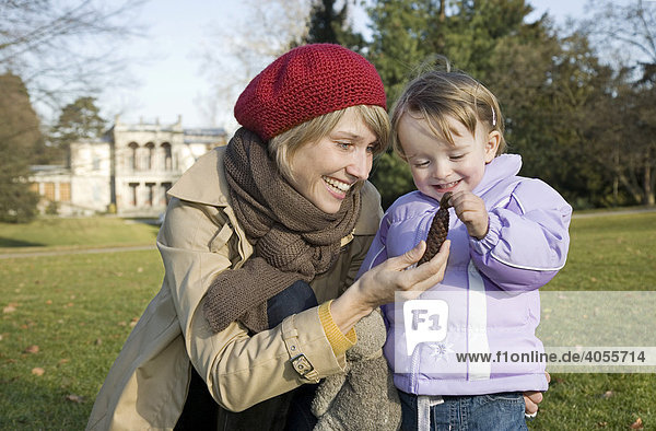 Mother and her 2-year-old daughter looking at a pine cone during a walk in the Rieter Park  in front of the Villa of the Rietberg Musuem in Zurich  Switzerland  Europe