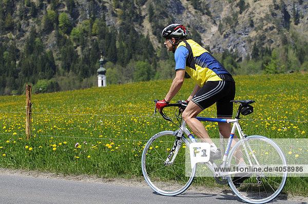 Rennradfahrer  Kirchturm von Kössen  Tirol  Österreich  Europa