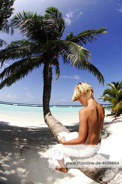 Junge liest auf Palme  Kurumba Resort  Malediven  Indischer Ozean  MR