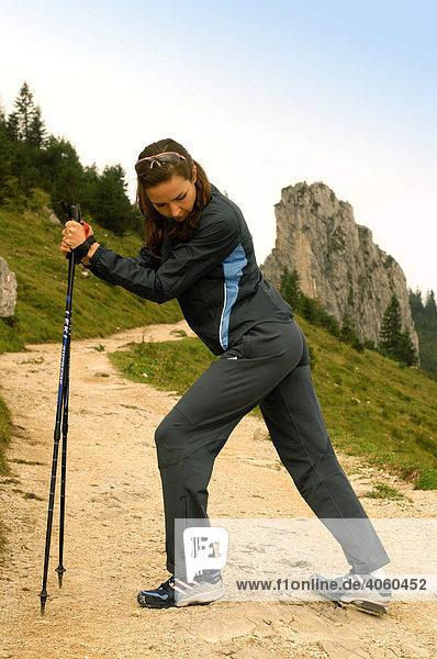 Woman stretching  nordic walking  Kampenwand  Chiemgau  Upper Bavaria  Bavaria  Germany  Europe