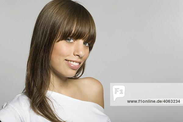Young  dark-haired woman smiling at camera  grey backdrop