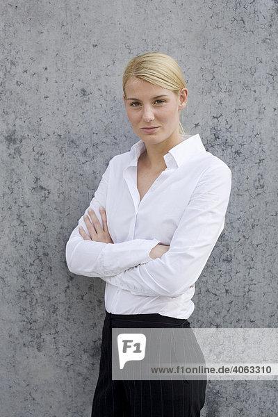 Junge blonde Frau im Business-Look steht mit verschränkten Armen vor einer grauen Wand