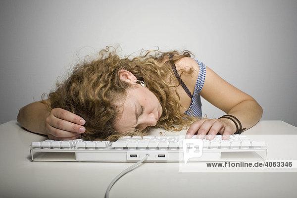 Junge langhaarige Frau liegt mit dem Kopf vor einer Computertatstatur auf einem Tisch