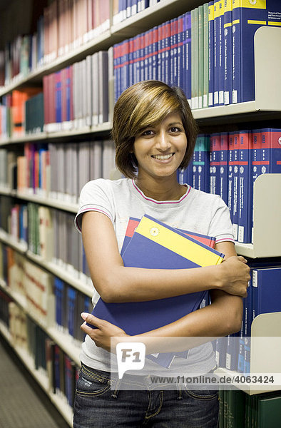 Junge dunkelhaarige Frau  Studentin  steht mit zwei Büchern im Arm vor einem Bücherregal in einer Bibliothek
