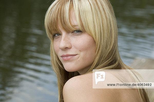Portrait einer jungen blonden Frau am Wasser