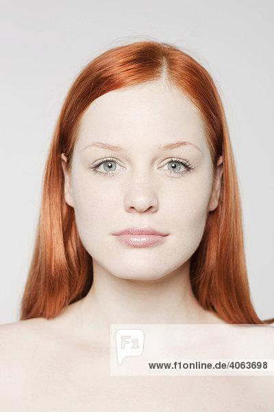 Portrait einer jungen rothaarigen Frau vor Weiß