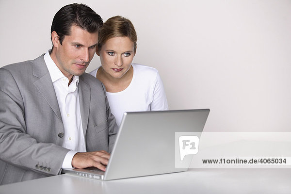 Frau mit ernstem Blick und Mann am Laptop