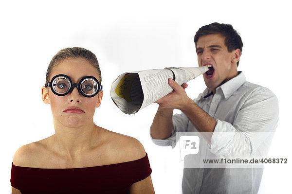 Mann mit Flüstertüte schreit Frau an