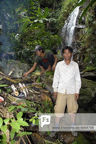 Laoten grillen Fisch im Dschungel bei einem Wasserfall  Phongsali Provinz  Laos  Südostasien