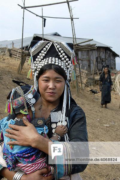 Mutter der Akha Meuo Ethnie gekleidet in traditionelle Tracht hält ihr Baby im Arm  hinten die Großmutter  Ban Chakhampa  Phongsali Provinz  Laos  Südostasien