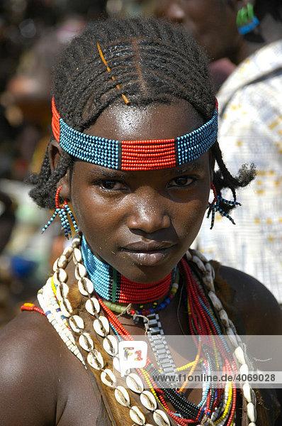 Portrait  Mädchen mit buntem Kopfschmuck und Kaurimuscheln als Halskette  Markt von Dimeka  Äthiopien  Afrika