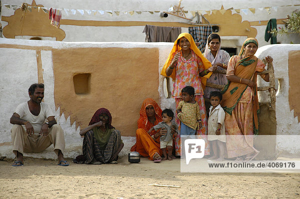 Colourfully dressed family standing and sitting at the wall of a village  women wearing saris  Thar Desert  Rajasthan  India  South Asia