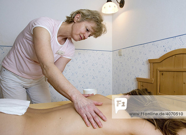 Junge Frau liegt im Wellnessbereich und wird massiert