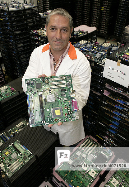 Computer production  employee holding a mainboard towards the camera  at the mainboard production of Fujitsu Siemens GmbH in Augsburg  Bavaria  Germany  Europe