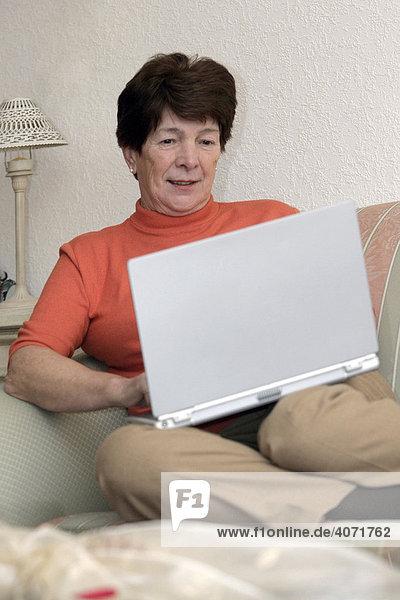 Woman  elderly  senior citizen  sitting on a living room sofa  on a laptop