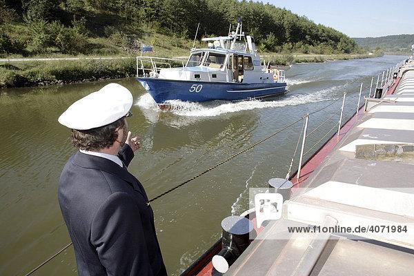 Polizeibeamter der Wasserschutzpolizei auf dem Gütermotorschiff Stadtprozelten winkt das Polizeiboot WSP 50 heran  auf dem Main-Donau-Kanal bei Beilngries  Bayern  Deutschland  Europa