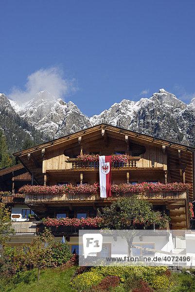 Mit Blumen und Tirolfahne geschmücktes Haus in den Tiroler Alpen  hinten verschneites Bergmassiv  Alpbach  Tirol  Österreich  Europa