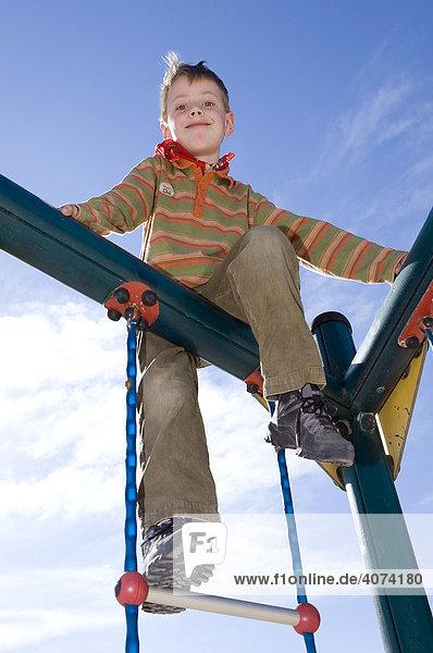 6-year-old boy climbing on a jungle gym