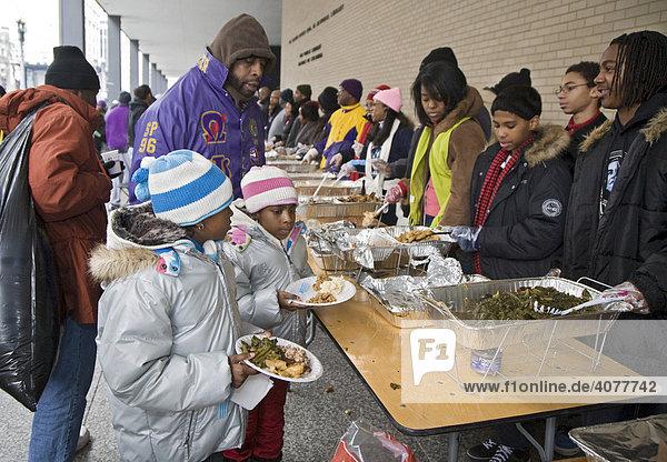 Freiwillige in einer Freiluft-Suppenküche verteilen Essen an ...