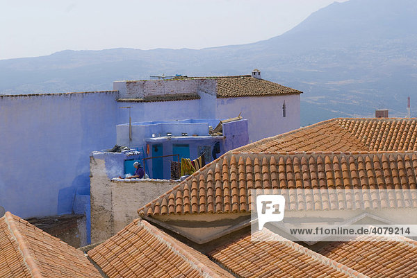 Roofs and a laundrywoman in Chefchaouen  Marocco  Africa