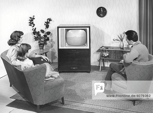 Modellfamilie in Modellwohnzimmer vor Fernsehgerät  historische Aufnahme  ca. 1955