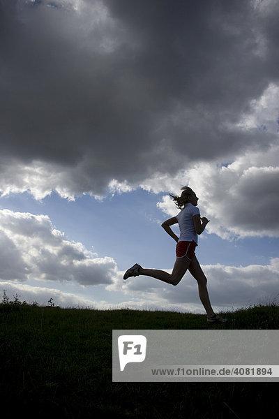 Frau beim Lauftraining als Silhouette vor Himmel mit dunklen Wolken