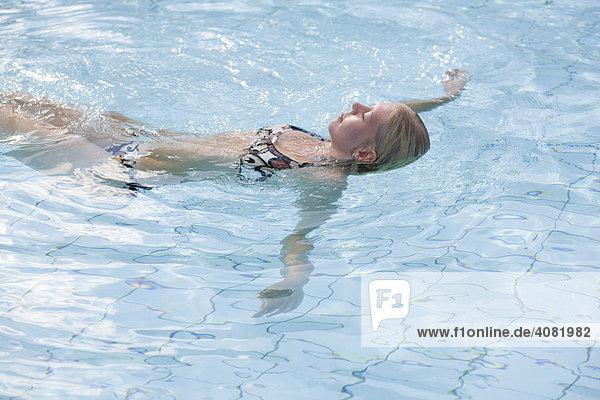 Blonde Frau schwimmt im Wasser