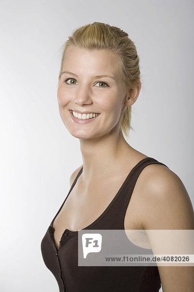 Portrait einer lachenden jungen Frau im braunen Shirt