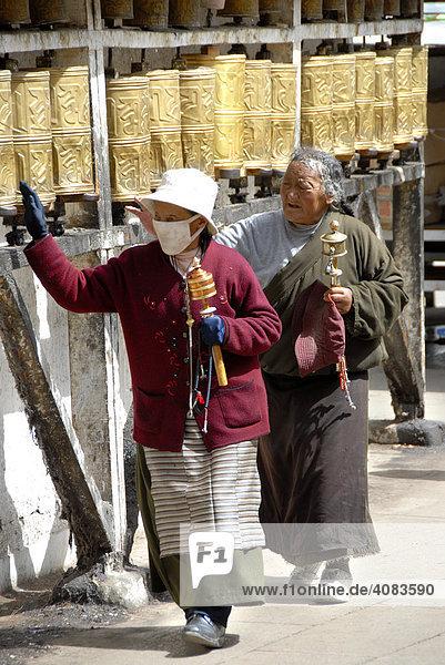 Tibetische Pilger drehen Gebetsmühlen Mani Lakhang Tempel Lhasa Tibet China