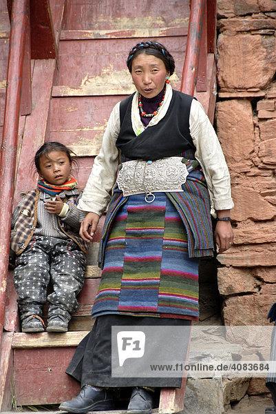 Tibetische Pilgerin in Tracht mit Kind vor Holztreppe Kloster Rongbuk Tibet China
