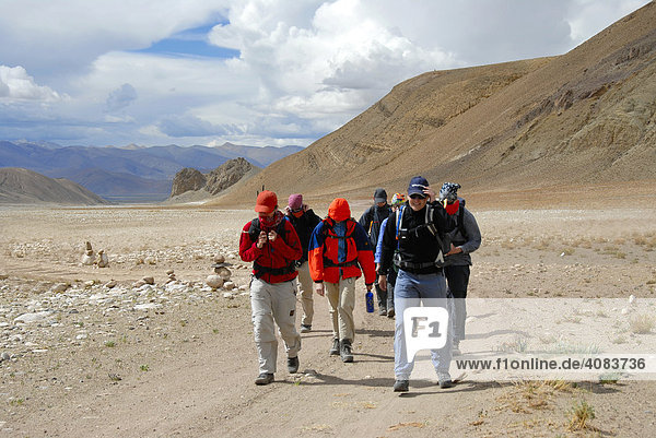 Trekking group passes wide river plain in heavy storm near Lungchang Tibet China