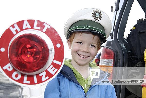 Junge hat sich mit einer Polizeimütze verkleidet und spielt Polizist