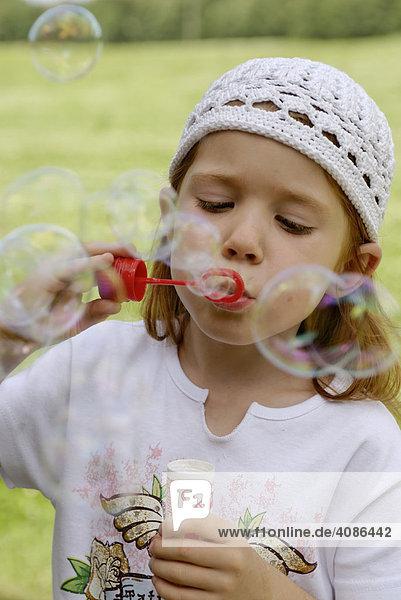 Junges Mädchen beim Seifenblasen pusten